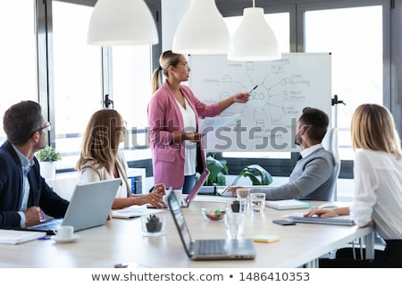 Stock photo: Attractive young businesswoman pointing