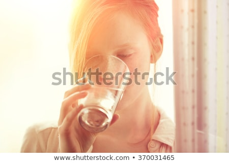 Young Woman Drinking Glass Of Water In Modern Kitchen Stock photo © monkey_business
