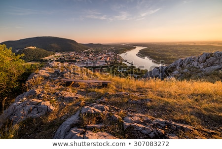 view of lit small city with river from the hill at sunset stock photo © kayco