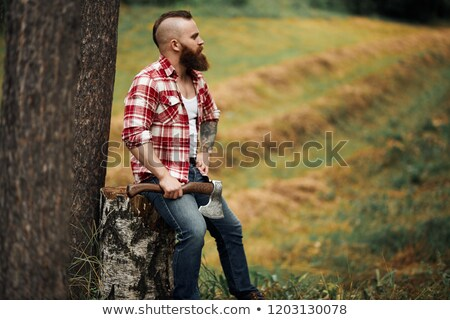 handsome bearded lumberjack holding axe in mountain winter forest stock photo © deandrobot