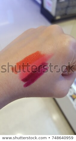 Makeup artist testing lip gloss and choosing color for woman Stock photo © deandrobot