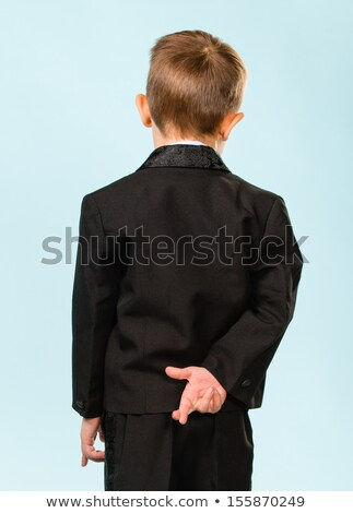 Little kid with fingers crossed behind back Stock photo © zurijeta