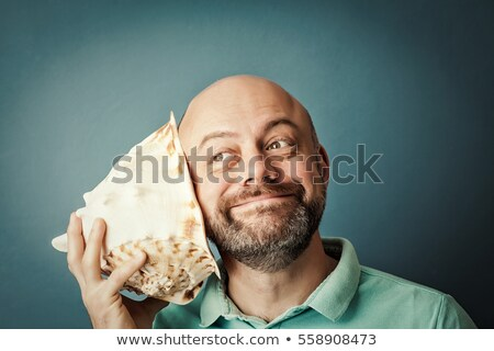 Man listening to sound of sea in shell Stock photo © ozgur