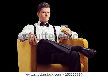 Jeune homme séance fauteuil potable whiskey image Photo stock © deandrobot