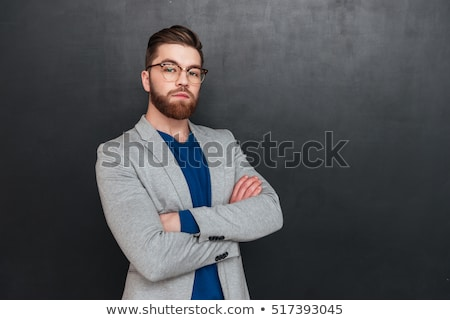 Strict serious young man in glasses standign with arms crossed Stock photo © deandrobot