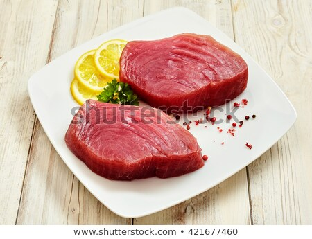 Red tuna steak with lemon on wood background Stock photo © Yatsenko