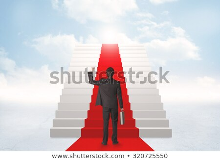 Young businessman climbing stairs and red carpet Stock photo © Elnur