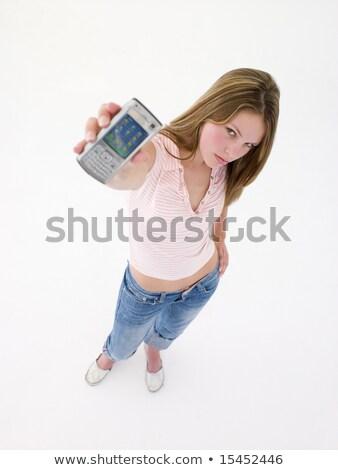 tinilány · magasra · tart · mobiltelefon · lány · mosoly · gyerekek - stock fotó © monkey_business