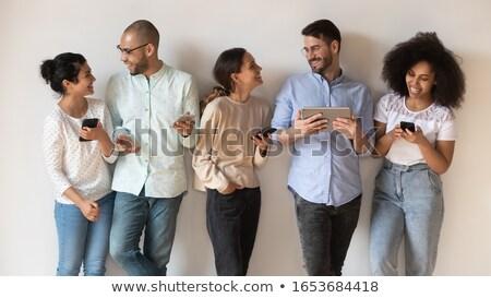 Foto stock: Ila · de · cinco · amigos · usando · telefones · celulares · sorrindo