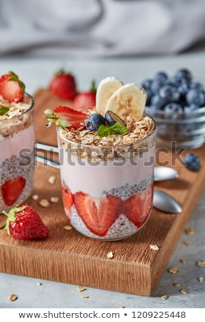 natural organic ingredients for healthy breakfast in a glasses   oat granola banana and strawberry stock photo © artjazz