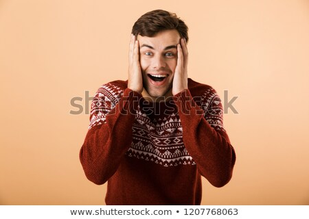 Image of surprised man 20s with stubble wearing knitted sweater  Stock photo © deandrobot