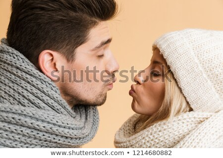 Cute young loving couple in scarfs and hat isolated over beige background kissing. Stock photo © deandrobot