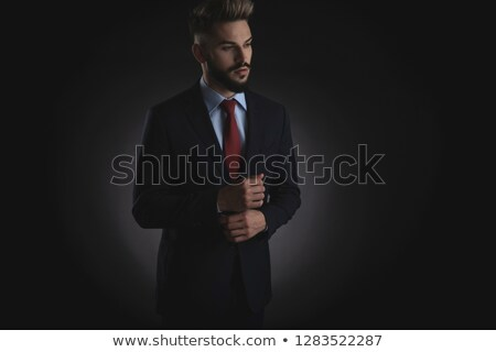 surprised businessman arranges suit cuffs and looks down to side Stock photo © feedough