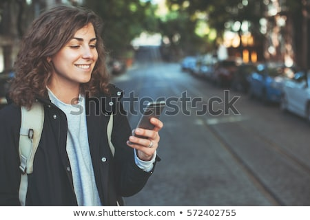 Beautiful brunette walking at street and talking to phone. stock photo © studiolucky