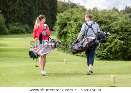 rear view of couple carrying golf bag stock photo © kzenon