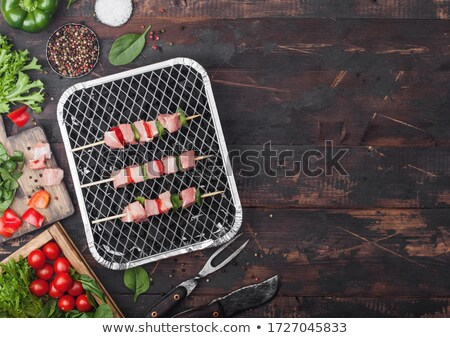 raw pork kebab with paprika on disposable coal bbq grill with fresh vegetables on wooden background stock photo © denismart