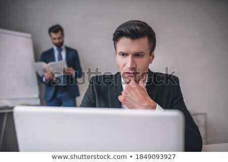 young serious white collar worker reading paper and brainstorming stock photo © pressmaster