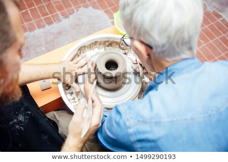 Over view at senior woman spinning clay on a wheel with teacher  Stock photo © boggy