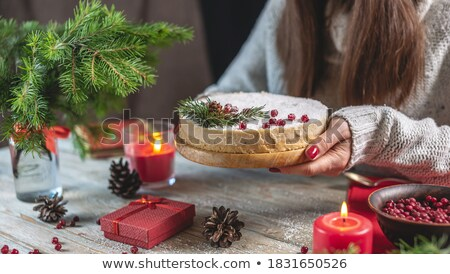 Woman holding Christmas Cake decorated with berries Stock photo © dashapetrenko