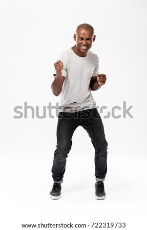Emotional young african man standing isolated make winner gesture Stock photo © deandrobot