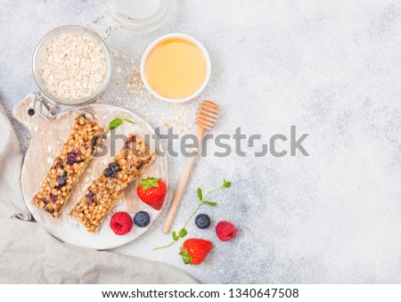 Organic cereal granola bar with berries on round vintage board with honey spoon and jar of oats on m Stock photo © DenisMArt
