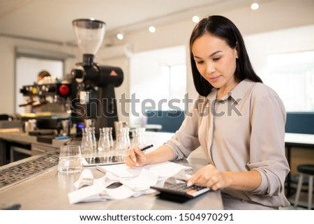 Pretty young accountant counting total sum of receipts at the end of working day Stock photo © pressmaster