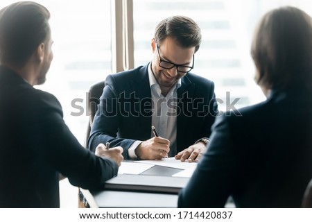 Confident man signing contract of loan agreement document with b Stock photo © Freedomz