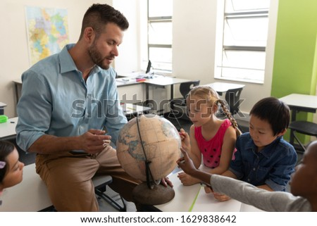 Male teacher teaching his kids about geography by using globe in classroom of elementary school Stock photo © wavebreak_media