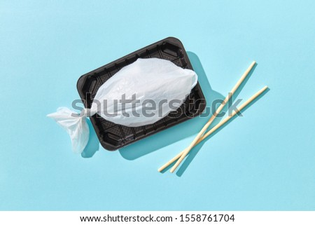 Plastic bag in a shape of fish on a plastic plate with chopsticks. Stock photo © artjazz