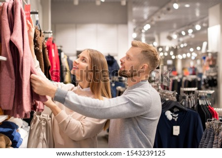 Young couple in casualwear looking at new seasonal collection of clothes Stock photo © pressmaster