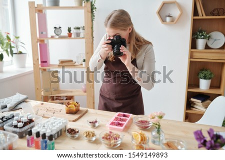 Young woman shooting ingredients and aromatic stuff for making handmade soap Stock photo © pressmaster