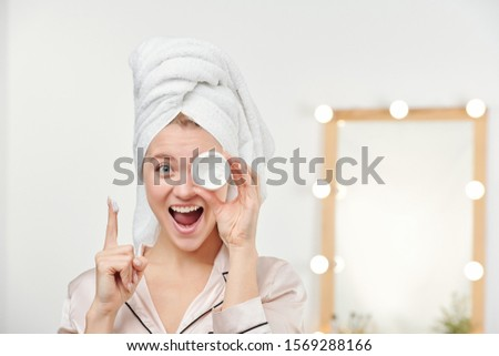 Ecstatic girl with towel on head holding jar of facial moisturizer by left eye Stock photo © pressmaster