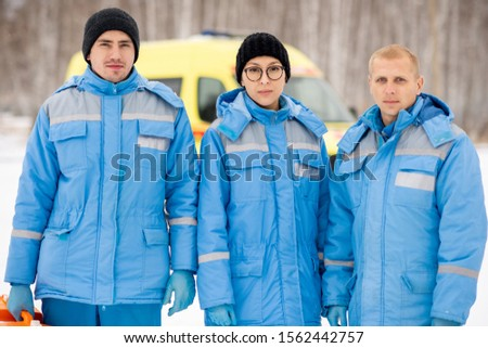 Brigade of young paramedics in blue workwear and gloves holding first aid kits Stock photo © pressmaster