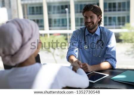 Rear view of disabled young mixed-race woman shaking hands with handsome Caucasian male doctor in ho Stock photo © wavebreak_media