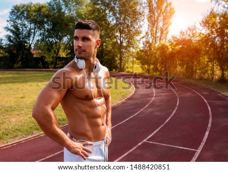 Workout, earphones and music concept. Attractive shirtless athlete with naked torso, put wireless he Stock photo © benzoix