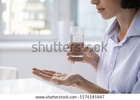 Tired businesswoman with headache going to have glass of water and painkiller Stock photo © pressmaster