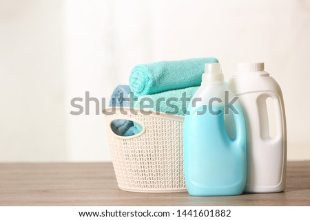 Stack of folded white towels and bottles with detergent against white background. Washing and cleanl Stock photo © vkstudio