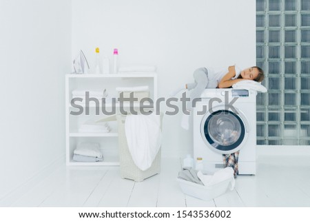 Female preschooler sleeps on washing machine, being tired with washing, poses in white big laundry r Stock photo © vkstudio