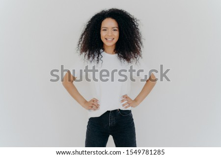 Photo of delighted curly woman keeps both hands on waist, smiles gently, has slim figure, wears whit Stock photo © vkstudio