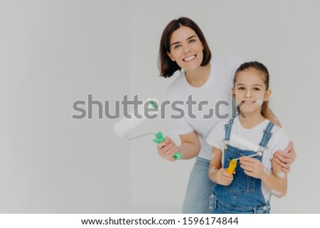 Family and house repairing concept. Positive caring mother cuddles child, have fun when refurbish wa Stock photo © vkstudio