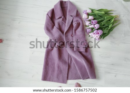 A pink coat lies on the wooden floor next to a bouquet of flowers Stock photo © ElenaBatkova
