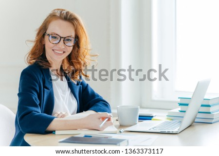 Self confident young female director plans work process, writes main theses in notepad, rewrites inf Stock photo © vkstudio