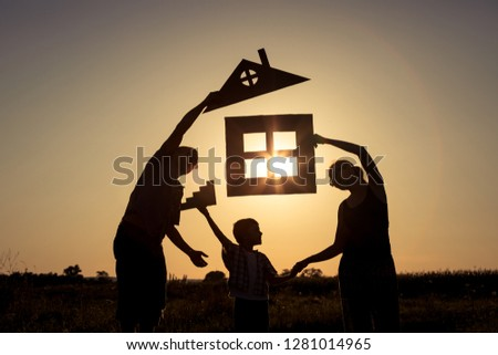 Happy family standing on the field at the sunset time. They buil stock photo © altanaka