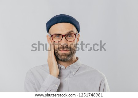 Blue eyed unshaven man raises eyebrow, keeps hand on cheek, looks happily, wears eyewear, dressed in Stock photo © vkstudio