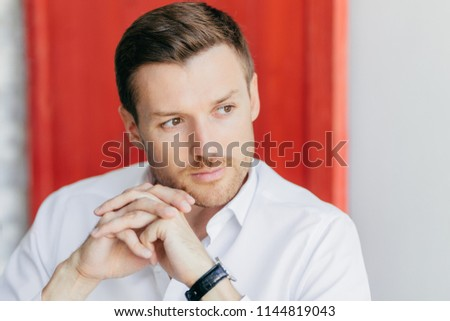 Pensive male director keeps hands presssed together, looks thoughtfully aside, being deep in thought Stock photo © vkstudio