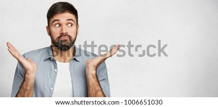 Indoor shot of hesitant bearded man shrugs shoulders, looks unce Stock photo © vkstudio