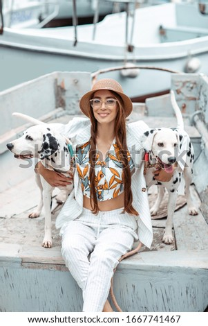 Girl walks with pet, adult Dalmatian on the waterfront with water transport. Stock photo © ElenaBatkova