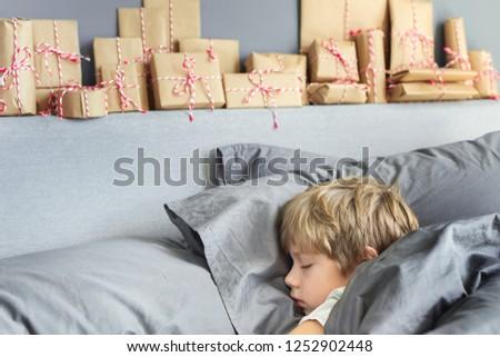 Little blond boy sleeping on a bed and home made advent calendar on a shelf. Winter seasonal traditi Stock photo © galitskaya