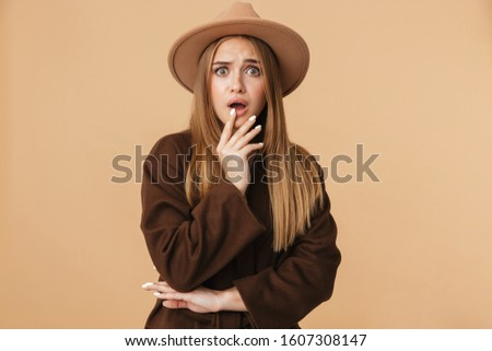 Image of young stressed girl wearing hat expressing wonder with  Stock photo © deandrobot