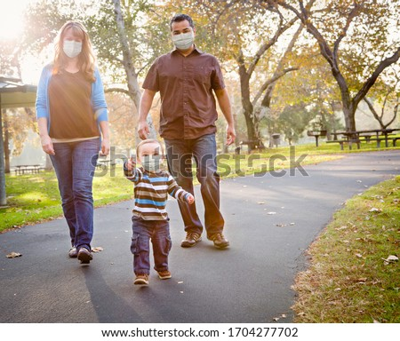 Happy Mixed Race Ethnic Family Walking In The Park Wearing Medic Stock photo © feverpitch